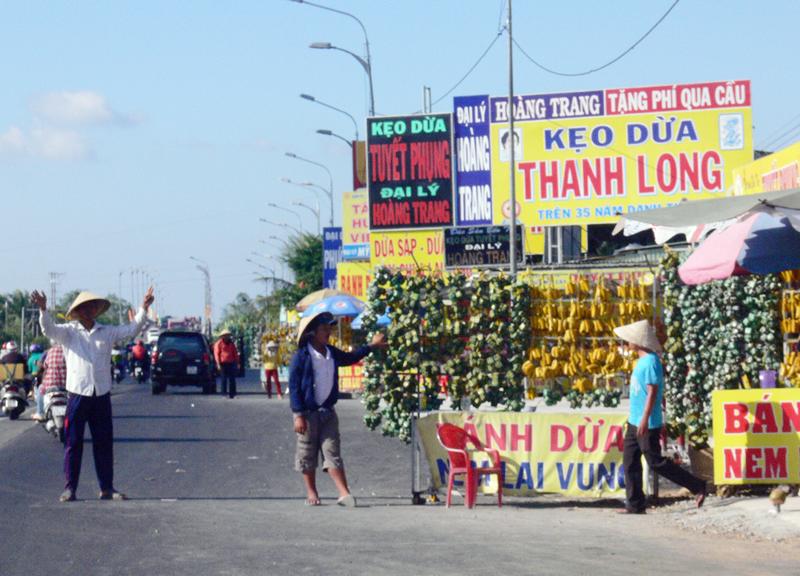 """Nhiều hộ buôn bán ra đường """"tiếp thị"""" làm cản trở giao thông, đoạn Tam Phước (Châu Thành)."""