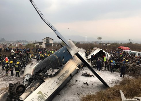 Lực lượng cứu hộ quanh xác máy bay ở sân vận động gần sân bay quốc tế của Kathmandu ngày 12-3  (Ảnh: Reuters).