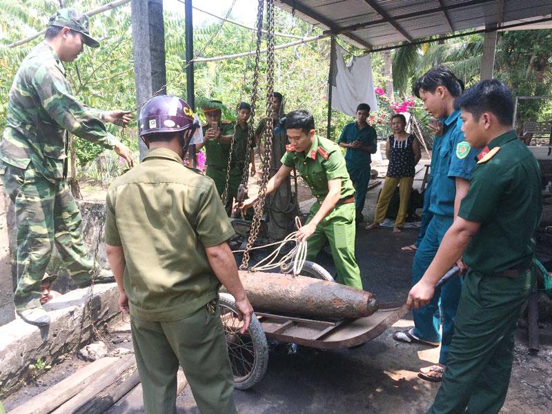 Lực lượng chức năng tổ chức thu gom quả bom. Ảnh: Đặng Thạch