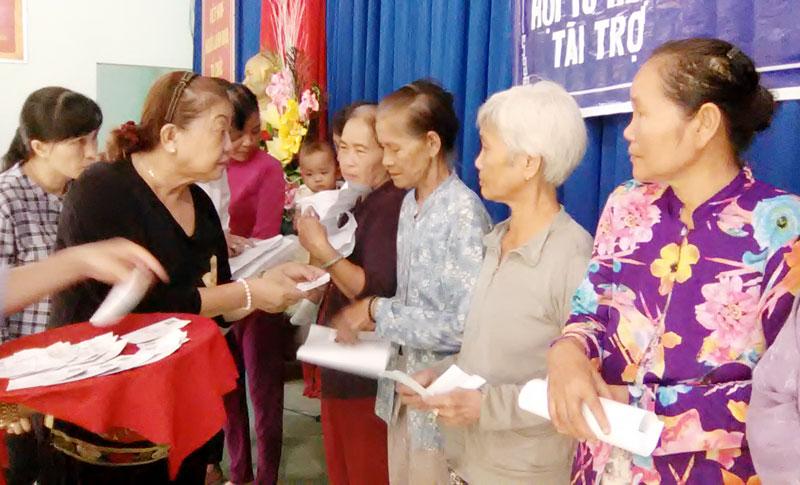 Đơn vị tài trợ trao thẻ bảo hiểm cho hộ cận nghèo. Ảnh: Văn Minh