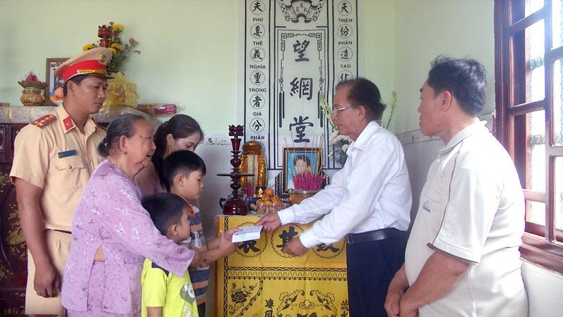 Đại diện Ban an toàn giao thông tỉnh trao tiền cho gia đình nạn nhân. Ảnh: Văn Minh