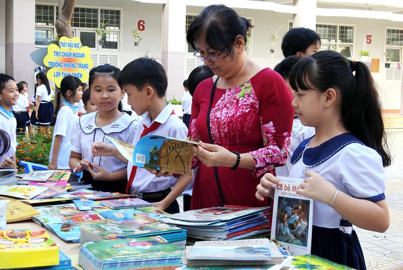 Giáo viên và các em học sinh tham quan, chọn mua sách tại ngày hội.