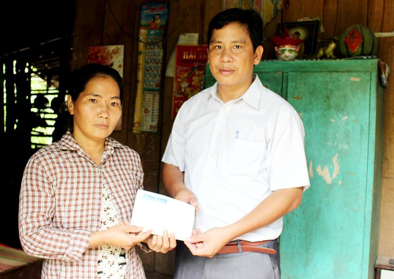 Chủ tịch UBND xã Phú Đức Ngô Thanh Quý trao tiền của bạn đọc hỗ trợ cho chị Nguyễn Thị Loan. Ảnh: H. Đức