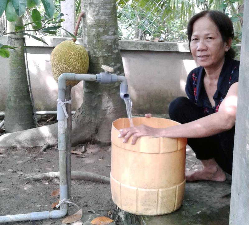Bà Lê Thị Phụng Loan bên nguồn nước máy đã được cải tiến chất lượng. Ảnh: HĐ