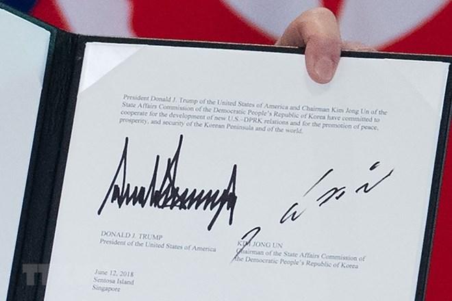 Văn kiện chung lưu lại chữ ký của Tổng thống Mỹ Donald Trump (trái) và của nhà lãnh đạo Triều Tiên Kim Jong-un (phải) tại Sentosa, Singapore ngày 12-6-2018. Nguồn: AFP/TTXVN