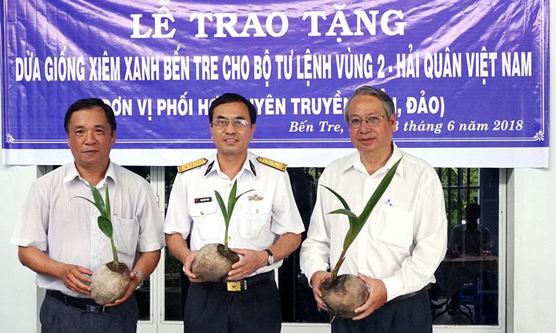 Trưởng Ban Tuyên giáo Tỉnh ủy Cao Văn Dũng (bìa phải), Thượng tá Phạm Minh Chiến và kỹ sư Nguyễn Văn Dũng (tài trợ 200 cây dừa giống xiêm xanh) tại lễ trao tặng. Ảnh: Q.Hùng