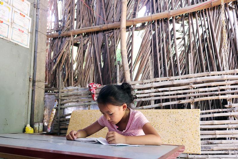 Bé Lê Thị Hà My học bài trong ngôi nhà đang xuống cấp.