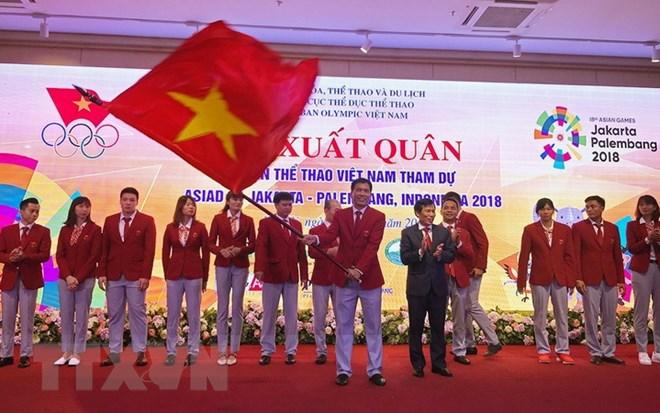 Ông Trần Đức Phấn, trưởng đoàn thể thao Việt Nam tham dự ASIAD 2018 nhận cờ từ Bộ trưởng Bộ Văn hóa Thể thao và Du lịch Nguyễn Ngọc Thiện. (Ảnh: Trọng Đạt/TTXVN)