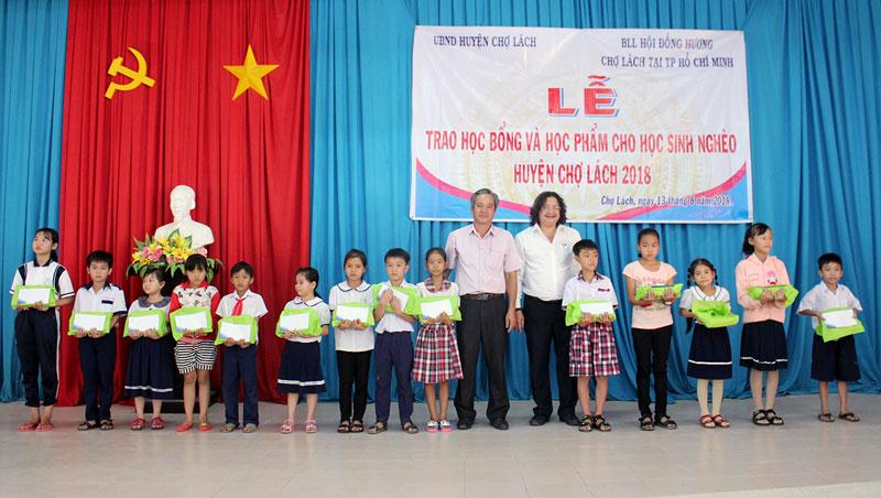 Ông Nguyễn Minh Đức và ông Nguyễn Minh Nhựt trao học bổng và học phẩm cho học sinh vượt khó. Ảnh: Cao Khiết