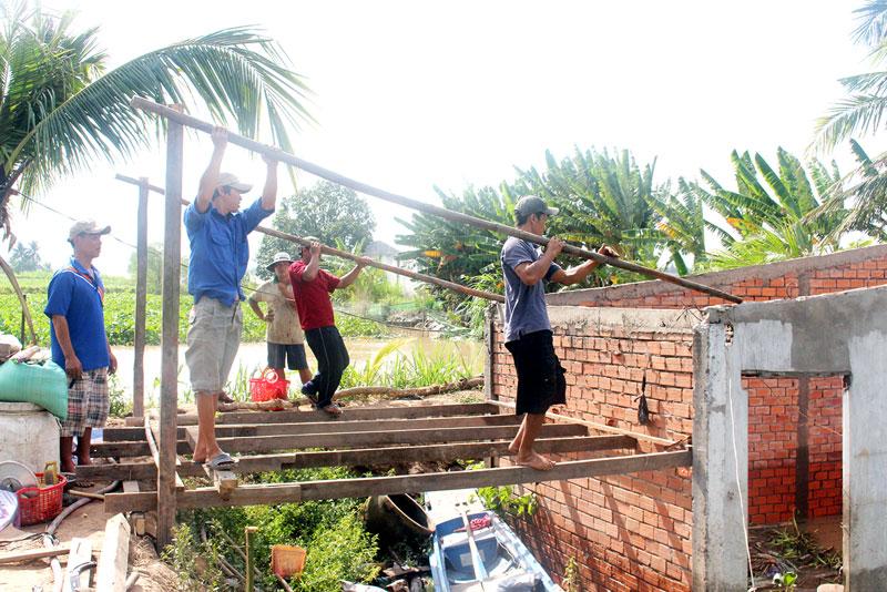 Người dân địa phương giúp gia đình anh Ngô Chung Hoàng Phương tháo dỡ, di dời nhà ở. Ảnh: Đ.Chính