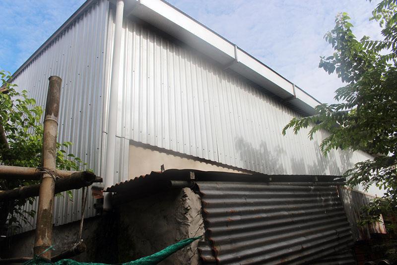 Nước mưa trên mái nhà kho chảy vào máng xối và theo ống chảy trực tiếp xuống nhà ông Thế gây ngập úng. Ảnh: PV