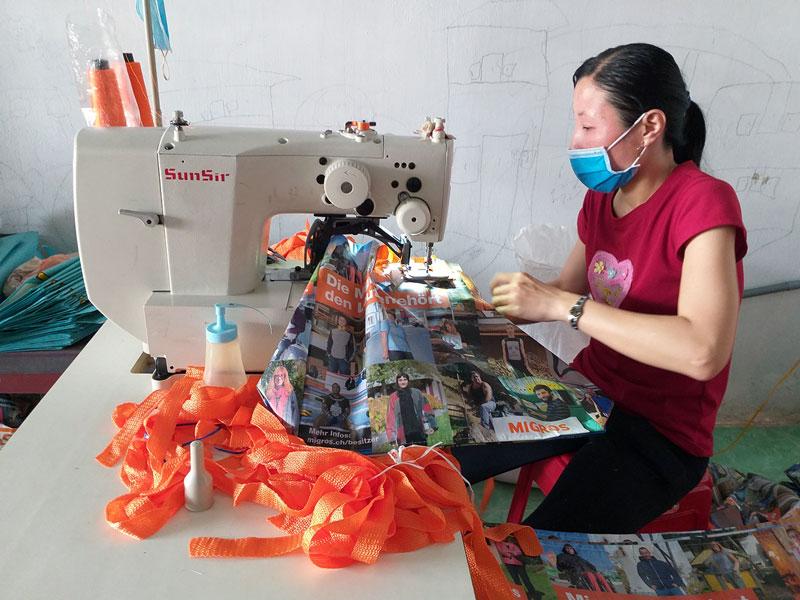 Thợ may đang thực hiện khâu đóng quai túi trên máy điện tử.