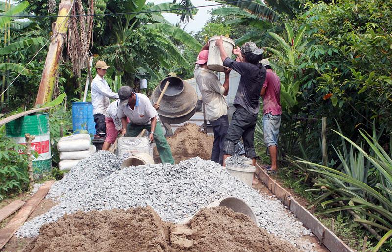 Thi công xây dựng đường bê-tông trên đê ấp Phú Ninh. Ảnh: H. Đức