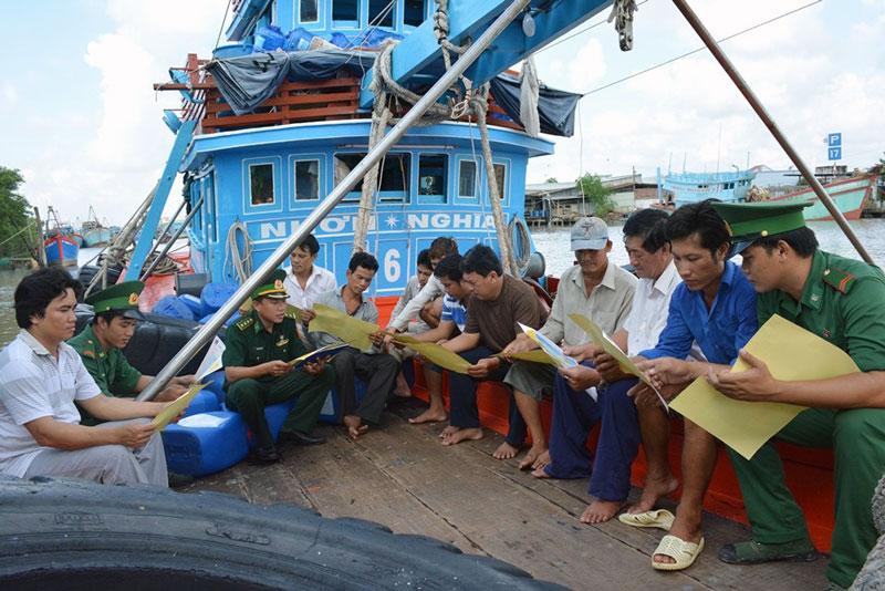 Cán bộ, chiến sĩ Trạm Kiểm soát biên phòng Bình Thắng tuyên truyền cho ngư dân về Chỉ thị số 01 của Thủ tướng Chính phủ. Ảnh: Biên Cương