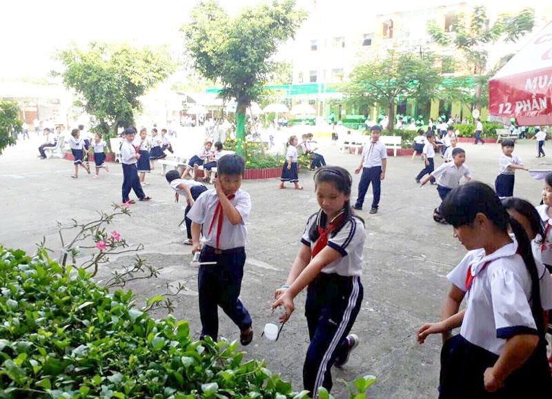 Học sinh Trường Tiểu học Chu Văn An nhặt rác trong giờ chơi.