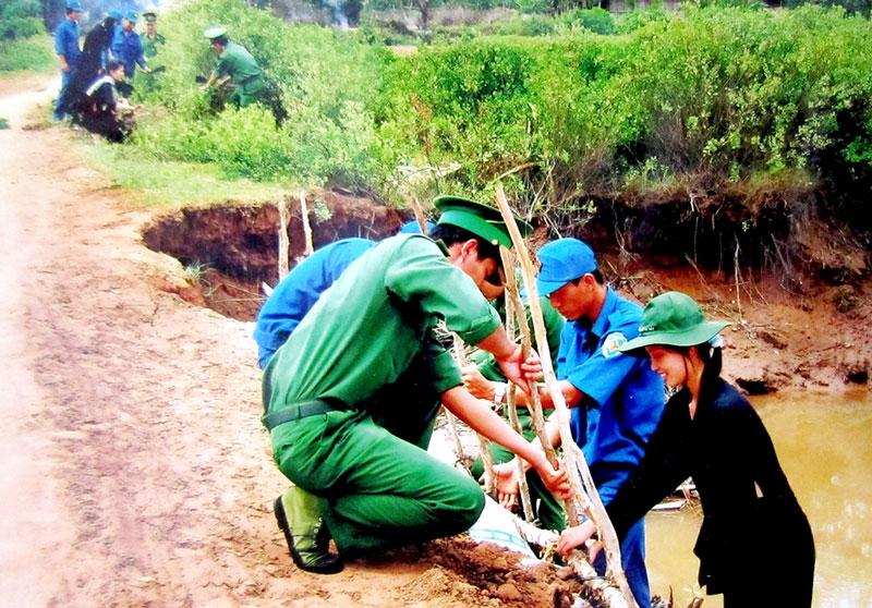 Cán bộ, chiến sĩ Đồn Biên phòng Cổ Chiên cùng phụ nữ, dân quân gia cố đường nông thôn.