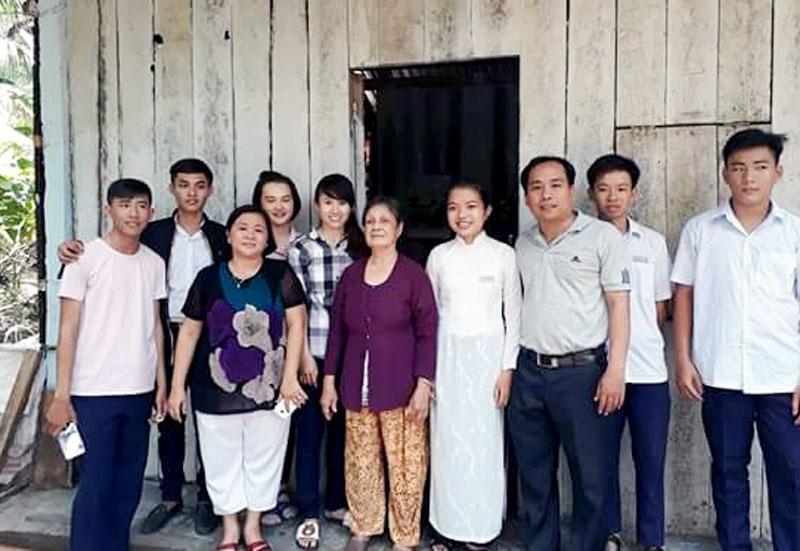 Chị Liên (thứ 3, từ trái sang) cùng các mạnh thường quân đóng góp tiền, công lao động sửa chữa nhà cho cụ bà Nguyễn Thị Lợi.