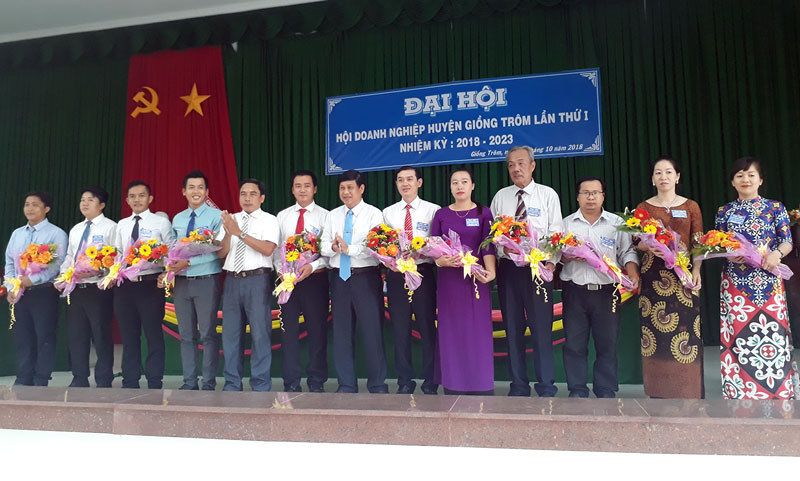 Lãnh đạo huyện Giồng Trôm tặng hoa chúc mừng 11 thành viên Ban chấp hành Hội Doanh nghiệp huyện. Ảnh: Kim Phụng