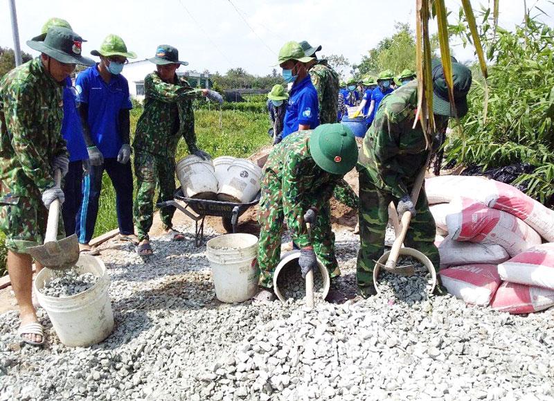 Cán bộ, chiến sĩ tham gia làm đường giao thông nông thôn tại xã Tân Thiềng nhân chuyến về nguồn. Ảnh: Đặng Thạch