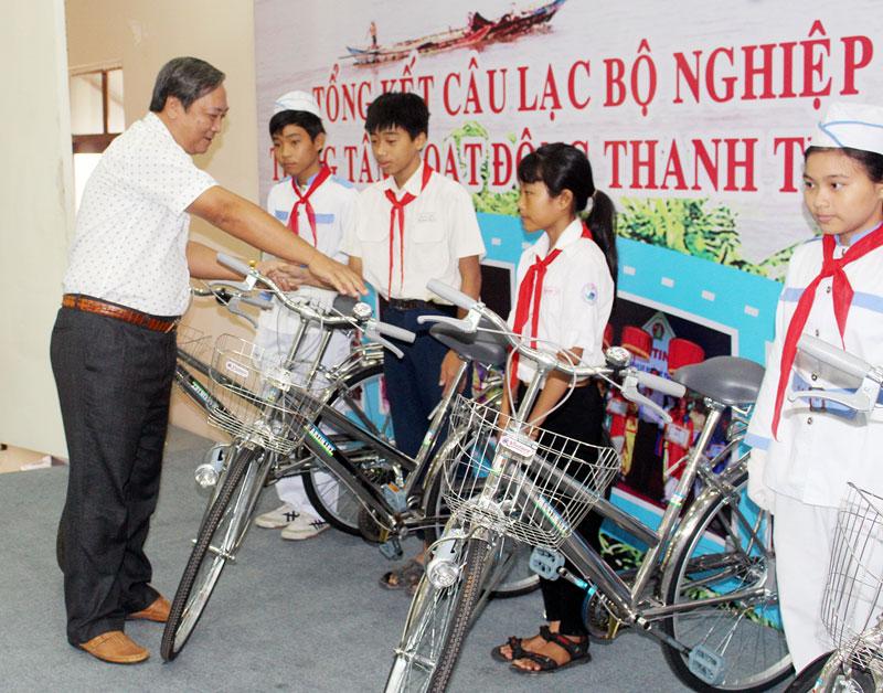 Phó chủ tịch UBND tỉnh Nguyễn Hữu Phước trao xe đạp cho thiếu nhi nghèo.