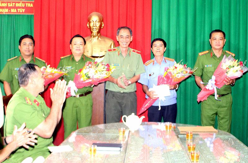 Thiếu tướng Nguyễn Văn Hoàng trao tặng hoa và tiền thưởng đột xuất cho cán bộ, chiến sĩ có thành tích phá án. Ảnh: H. Đức