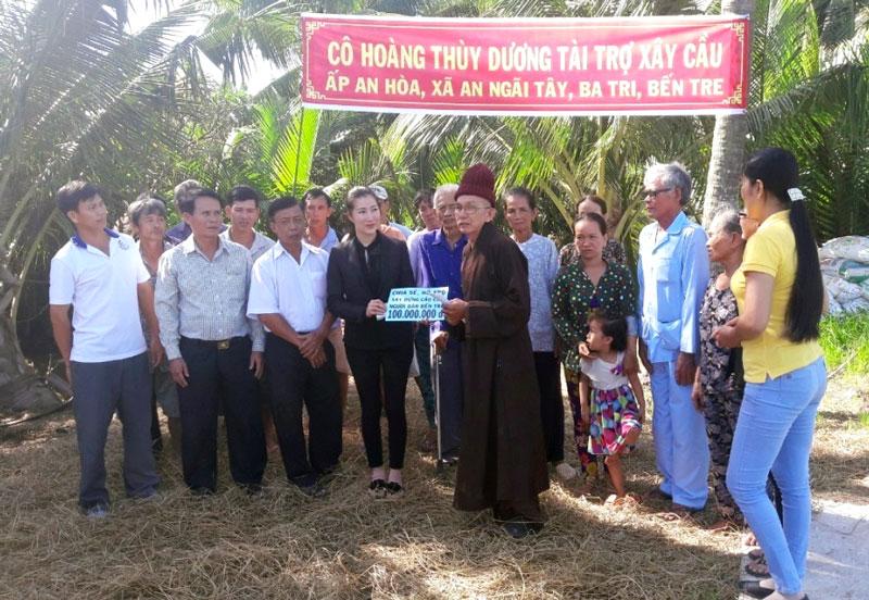 Cô Hoàng Thùy Dương trao biểu trưng kinh phí xây dựng cầu cho địa phương. Ảnh: Minh Đức