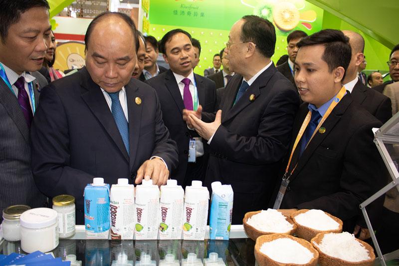 Thủ tướng Nguyễn Xuân Phúc quan tâm các sản phẩm dừa Vietcoco tại gian hàng Công ty TNHH Chế biến dừa Lương Quới. Ảnh: CTV