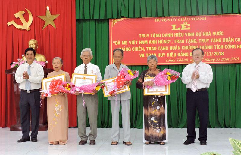 Ông Huỳnh Quang Triệu (bìa phải), ông Trương Minh Nhựt (bìa trái) trao Huy hiệu Đảng cho 4 đảng viên 50 tuổi Đảng. Ảnh: P. Tuyết