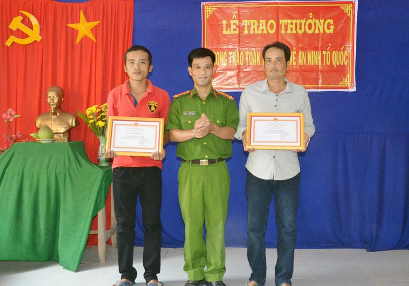 Đại diện lãnh đạo Công an huyện Chợ Lách trao giấy khen cho anh Phong và anh Nghĩa.