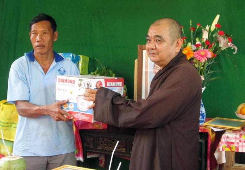 Đại diện nhà tài trợ tặng quà cho gia đình. Ảnh: Thảo Oanh