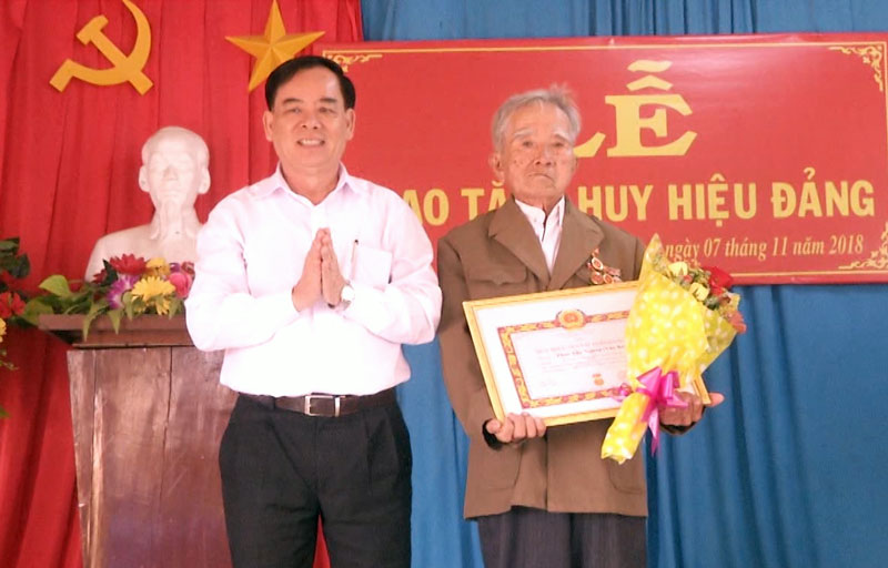 Phó bí thư Tỉnh ủy Trần Ngọc Tam trao tặng huy hiệu và hoa cho đồng chí Phan Văn Ngưng. Ảnh: Lê Chẳn