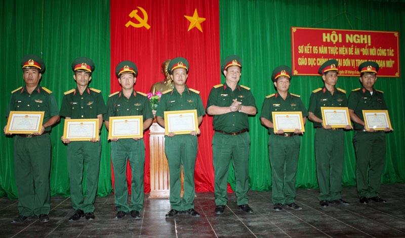 Đại tá Lê Văn Hùng - Chính ủy Bộ CHQS tỉnh trao thưởng cho các tập thể, cá nhân có thành tích qua 5 năm thực hiện đề án. Ảnh: Đặng Thạch