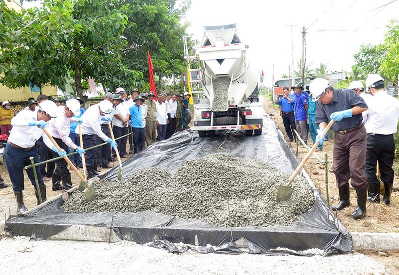 Các đại biểu ra quân thực hiện đổ bê-tông công trình đường ĐX.01 xã Mỹ Hưng.