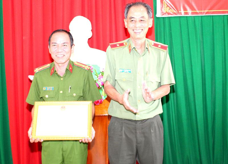 Thiếu tướng Nguyễn Văn Hoàng trao bằng khen của UBND tỉnh cho đại diện lãnh đạo Công an huyện Giồng Trôm. Ảnh: H. Đức