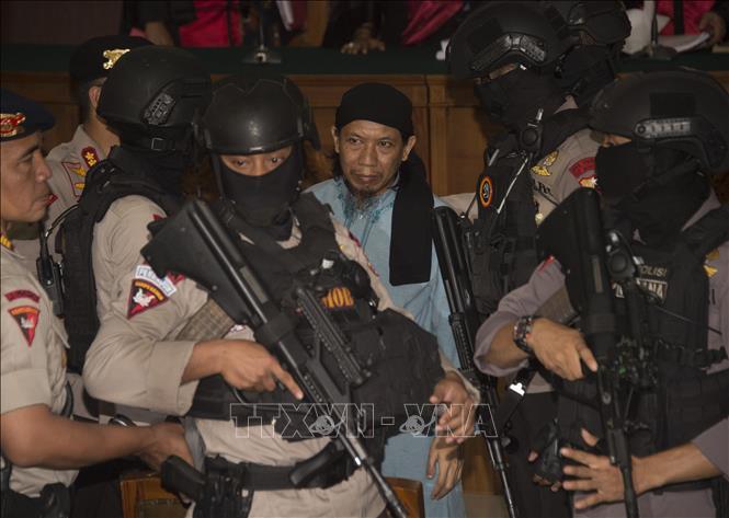 Cảnh sát áp giải giáo sĩ Hồi giáo Aman Abdurrahman (giữa) tới phiên tòa ở Jakartar, Indonesia ngày 22-6-2018. Ảnh: AFP/TTXVN