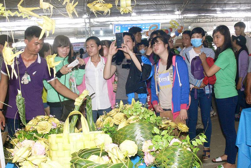 Khách du lịch thưởng lãm các sản phẩm làm từ lá dừa ở Chợ Lách. Ảnh: H.Hiệp