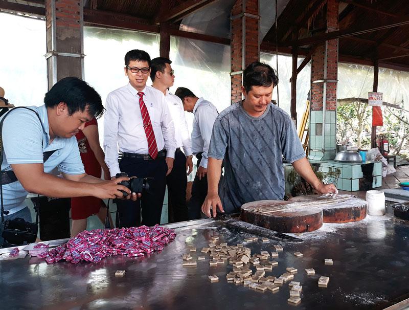Du khách tham quan quy trình làm kẹo dừa tại một điểm du lịch ở xã Tân Thạch, huyện Châu Thành. Ảnh: Thanh Đồng
