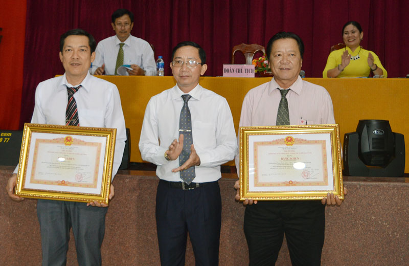 Giám đốc Sở Văn hóa, Thể thao và Du lịch Trương Quốc Phong trao bằng khen của Chính phủ cho 2 cá nhân tiêu biểu. Ảnh: A. Nguyệt