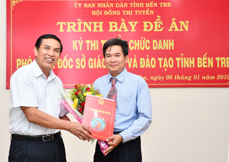 Chủ tịch UBND tỉnh Cao Văn Trọng tặng hoa và trao quyết định bổ nhiệm Phó giám đốc Sở Giáo dục và Đào tạo cho ông Bùi Minh Nhựt. Ảnh: Hữu Hiệp