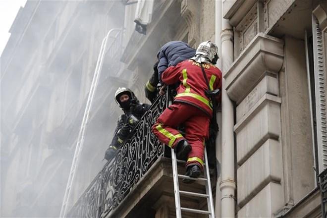 Lực lượng cứu hỏa hỗ trợ người mắc kẹt trong tòa nhà sau vụ nổ ở trung tâm Paris, Pháp ngày 12-1-2019. Ảnh: AFP/TTXVN