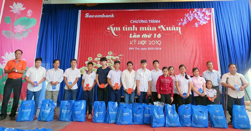 Đại diện lãnh đạo Sacombank trao quà cho các hoàn cảnh khó khăn. Ảnh: Trần Quốc