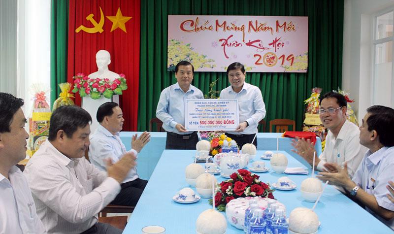 Chủ tịch UBND TP. Hồ Chí Minh Nguyễn Thành Phong trao bảng tượng trưng ủng hộ quà Tết cho người nghèo tỉnh.
