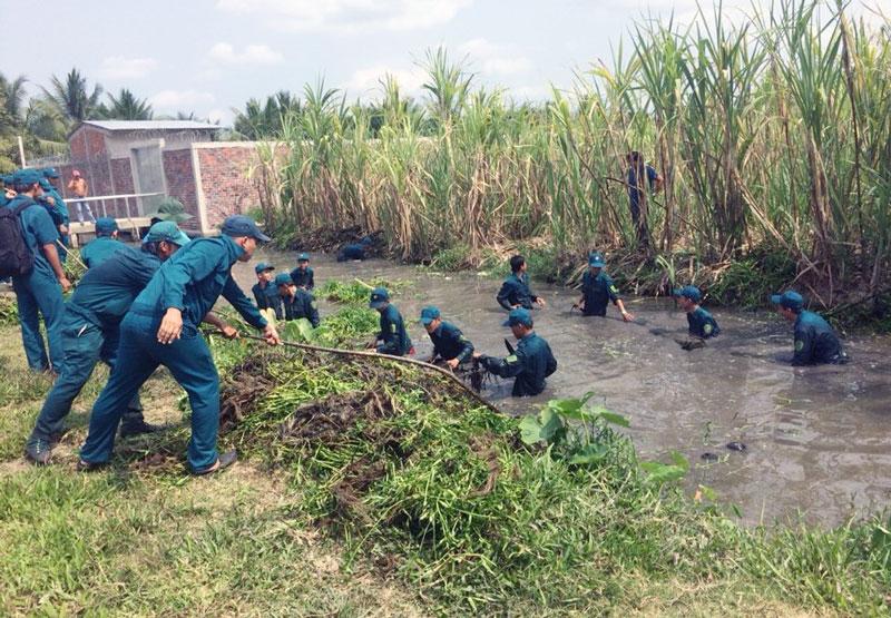 Lực lượng dân quân tự vệ huyện tham gia nạo vét kênh nội đồng trong mùa huấn luyện. Ảnh: Châu An