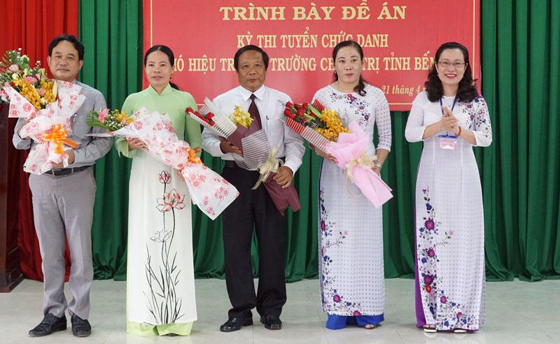 Hiệu trưởng Trường Chính trị tỉnh Nguyễn Trúc Hạnh trao hoa cho các ứng viên tham gia thi tuyển chức danh Phó hiệu trưởng trường. Ảnh: Q.Hùng