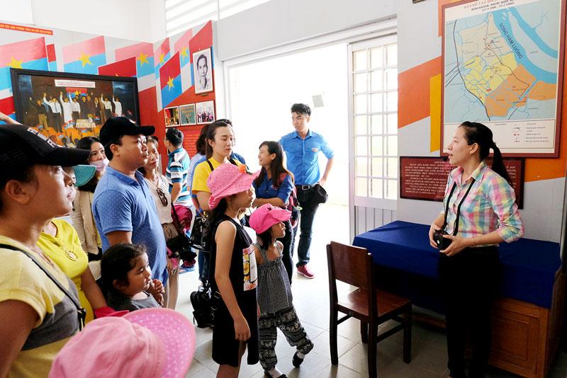Du khách đến tham quan, nghe thuyết minh tại Di tích Đồng Khởi (Mỏ Cày Nam). Ảnh: Quốc Thi