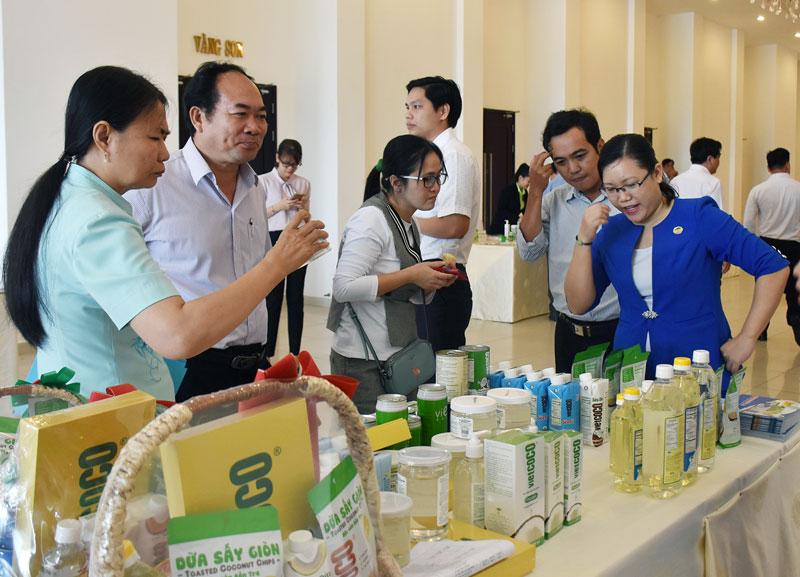 Đại biểu tìm hiểu các sản phẩm dừa của Công ty TNHH chế biến dừa Lương Quới được trưng bày tại một hội nghị do UBND tỉnh tổ chức.  Ảnh: C.Trúc