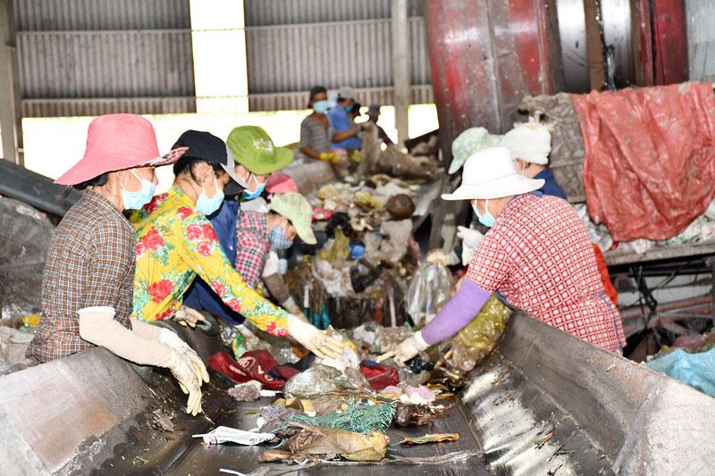 Công nhân đang phân rác ở công đoạn xử lý của Nhà máy rác Bến Tre.