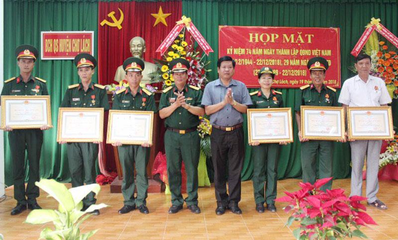 Lãnh đạo huyện và Ban CHQS huyện Chợ Lách trao huy chương Chiến sĩ vẻ vang cho các đồng chí có nhiều đóng góp trong xây dựng quân đội. Ảnh: Đặng Thạch