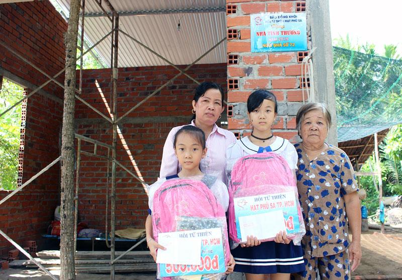 Chủ tịch Hội Chữ thập đỏ xã Tân Thanh Tây Lê Thị Rí (bên trái) trao quà hỗ trợ cho con gái của anh Tuấn.