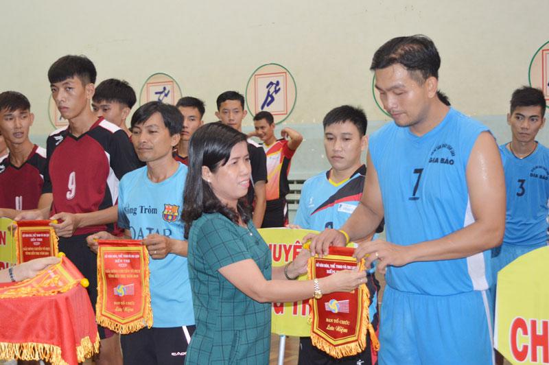 Ban tổ chức và đại biểu tham dự tặng cờ lưu niệm cho các đội tham dự giải.